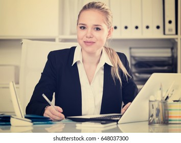 Smiling woman sitting at table and working on laptop in office