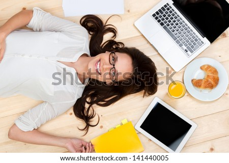 Smiling woman sitting thinking in an office chair as she mulls over a new idea in her mind