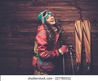 Smiling woman with skis and poles standing against wooden house wall