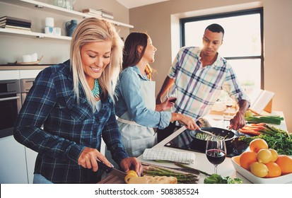 Smiling woman slicing ingredients for meal with diverse friends cooking asparagus spears in frying pan.