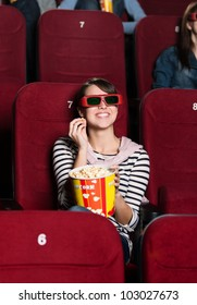 Smiling woman with a snack in the 3D movie