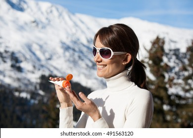 smiling woman in the snow with application of a solar cream