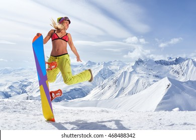 Smiling woman with snowboard jumping in mid air against of snowy mountains.Wearing bikini top and winter sportswear.