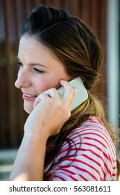 smiling woman speaking on her phone in her garden
