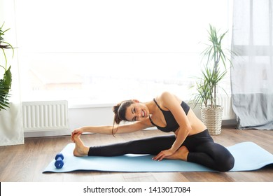 Smiling woman in sportswear exercising on fitness mat and looking at camera in living room