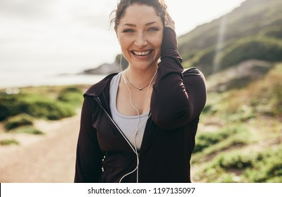 Smiling woman in sportswear standing outdoors after workout. Fitness woman listening music with earphones and looking at camera laughing.