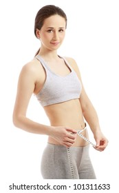 Smiling woman in sportswear with a tape measure, isolated on white background