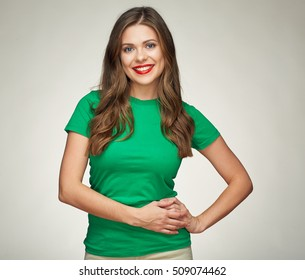 smiling woman standing against studio gray background. casual green dress. long hair.