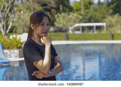 Smiling woman standing beside a pool.