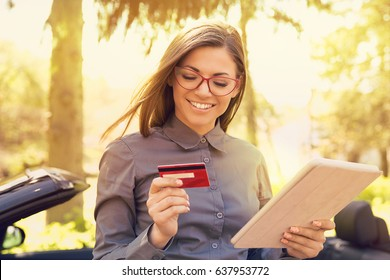 Smiling woman standing by her new car making online payment on her tablet computer outside on a sunny summer day