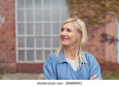 Smiling woman standing with folded arms looking up into the air watching something to the left of the frame with a brick building behind her