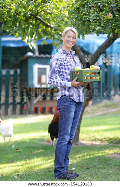 Smiling woman standing in the garden with a crate of apples
