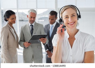 Smiling woman standing with a headset with colleagues working behind