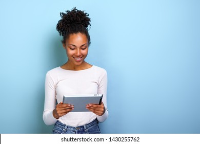 Smiling  woman standing with ipad looking at the screen and happily smile
