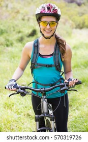 Smiling woman standing next to her bike in the countryside
