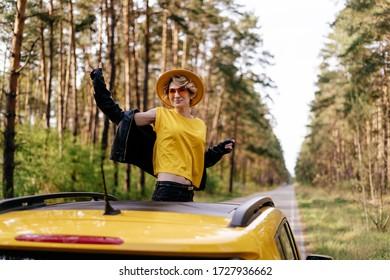 Lächelnde Frau aus gelbem Autosonnendach. Happy Girl in Leder Jacket und Sonnenbrille Lächeln. Sommerwald Abfahrt Roadtrip, Joyful Recreation. Aufgeregte kaukasische Weibchen im Fahrzeugdach
