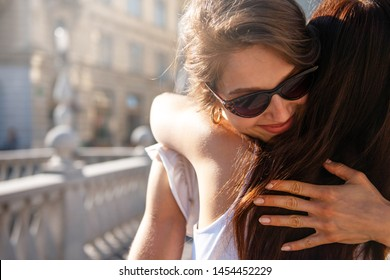 Smiling woman with sunglasses hugging her friend