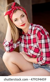 Smiling woman in sunglasses and red bandana and a plaid shirt. Beautiful girl with pretty smile.