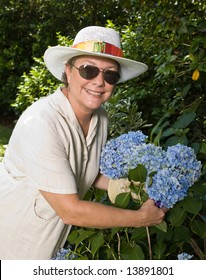 Smiling woman in sunglasses and straw hat picking big blue hydrangeas in her garden