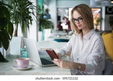 Smiling woman synchronizing smartphone and laptop