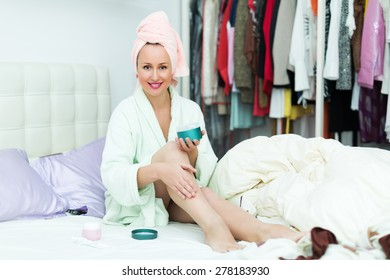 Smiling woman taking care of leg skin after shower
