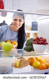 Mujer sonriente sacando una fruta fresca del refrigerador, concepto de comida saludable