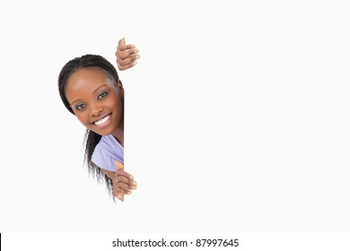 Smiling woman taking a look around the corner on white background