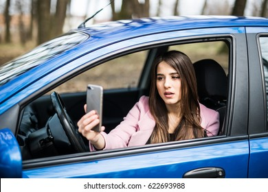 Smiling woman taking selfie picture with smart phone camera outdoors in car