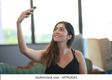 Smiling woman taking selfie with smartphone in the office