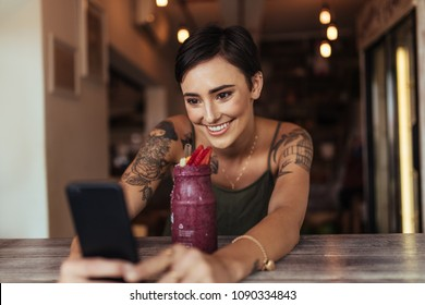 Smiling woman taking a selfie with a smoothie placed in front of her using a mobile phone for her food blog. Food blogger shooting photos for her blog at home.