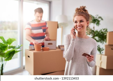 Smiling woman talking by mobile phone during moving out