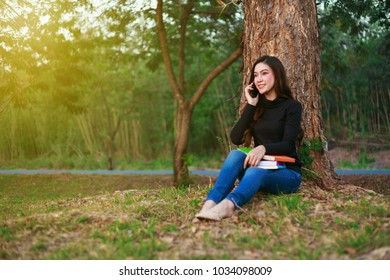 smiling woman talking on mobile phone in the park