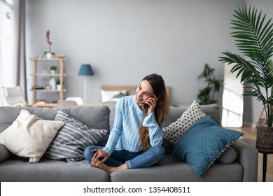 Smiling woman talking on the phone at home on the sofa. Feminine gossip on the smartphone.
