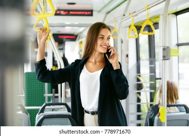 Smiling Woman Talking On Phone in Bus. Portrait Of Beautiful Happy Female In Stylish Casual Clothes Calling On Mobile Phone While Riding In Public Transport. High Quality Image.