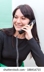 Smiling woman talking on telephone in office