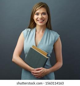 Smiling woman teacher holding book. isolated studio portrait.
