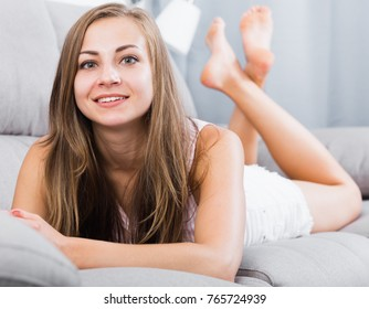 Smiling woman in tee-shirt and white jean shorts lying on sofa