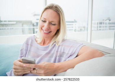 Smiling woman text messaging through mobile phone in living room