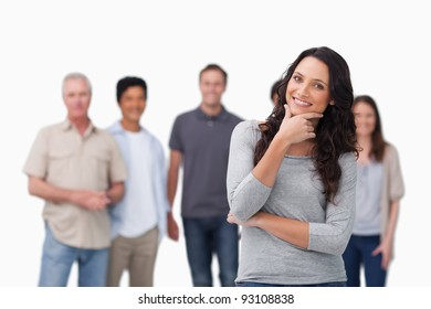 Smiling woman in thinkers pose and friends behind her against a white background