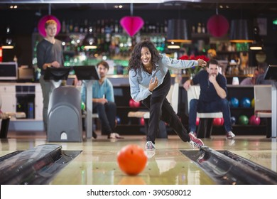 smiling woman throwed the ball at the bowling lane with her supporting friends