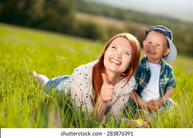 Smiling woman with thumb up lying  on green grass with her little son 2-3 year old. Young adults. Happy family. Happiness. Looking away.
