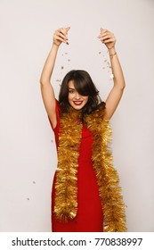 Smiling woman with tinsel throwing confetti and looking at camera in studio.