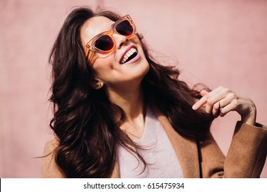 Smiling woman touches her hair posing in foxy sunglasses