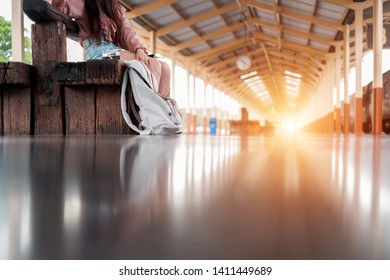 Smiling woman traveler with backpack holding vintage camera on holiday relaxation at the train station,relaxation concept, travel concept
