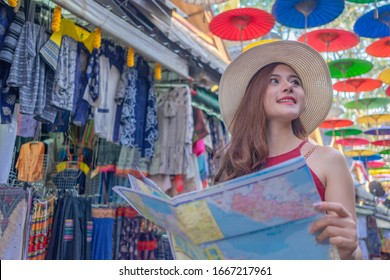 Smiling woman traveler in chiangmai market landmark thailand holding world map on holiday, relaxation concept, travel concept