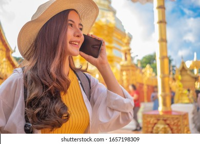 Smiling woman traveler in doi suthep temple chiangmai landmark in thailand holding smartphone with backpack on holiday, relaxation concept, travel concept