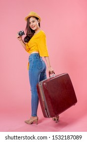 Smiling woman traveler holding camera and luggage in holiday on pink backgrounds, relaxation concept, travel concept