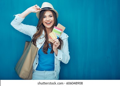 Smiling woman traveler holding passport with ticket and credit card. Blue wall back.