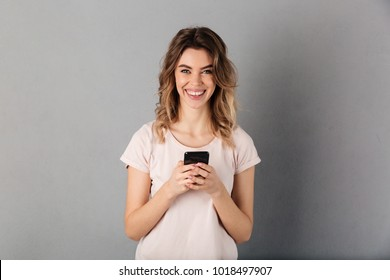Smiling woman in t-shirt holding smartphone and looking at the camera over grey background