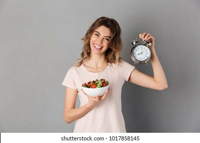 Smiling woman in t-shirt on diet holding plate with vegetables and alarm clock while looking at the camera over grey background